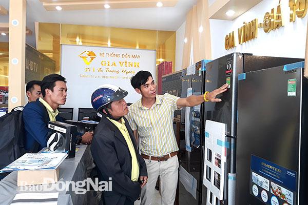 Anh Bùi Đức Vĩnh đang giới thiệu sản phẩm cho khách hàng tại một trung tâm thuộc hệ thống Điện máy Gia Vĩnh. Ảnh:V.Thế